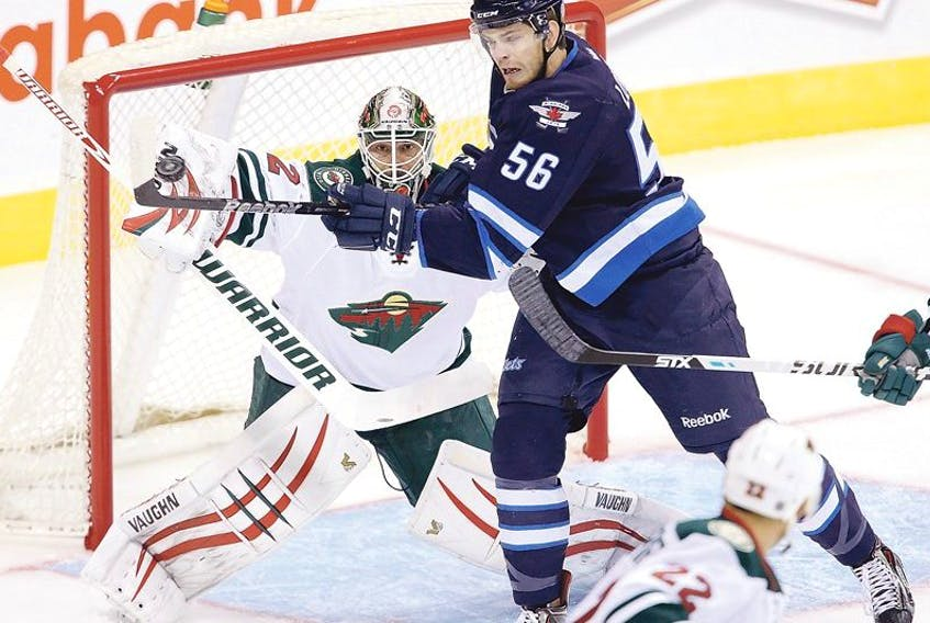 The Winnipeg Jets' Adam Lowry (56) tries to deflect the puck past Minnesota Wild goaltender Niklas Backstrom (32) during the teams' pre-season game in Winnipeg earlier this week. Last year, Lowry, the Jets third-round pick in 2011, had 17 goals and 33 points in 64 games for the St. John's IceCaps in his rookie season.