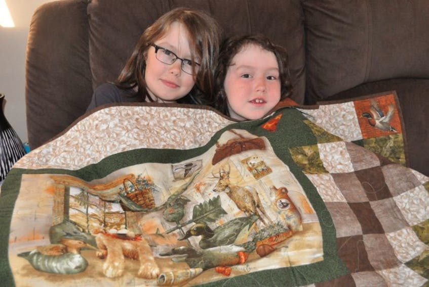 Grand Falls-Windsor's Mya Healey (left) and her little sister Lily snuggled up under a quilt made and donated to the family by a friend to help raise money for Team Mya. Mya was diagnosed with Juvenile Arthritis at the age of two, and is raising funds for the Arthritis Society before they family takes part in the Walk To Fight Arthritis on June 4 in Paradise.