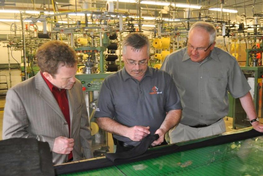 MP Scott Simms, left, Manager Fraser Stuckless, middle, and Point Leamington Mayor Wilfred Mercer discuss the making of protective sleeves, one of Superior Glove Works' 3000 product styles.