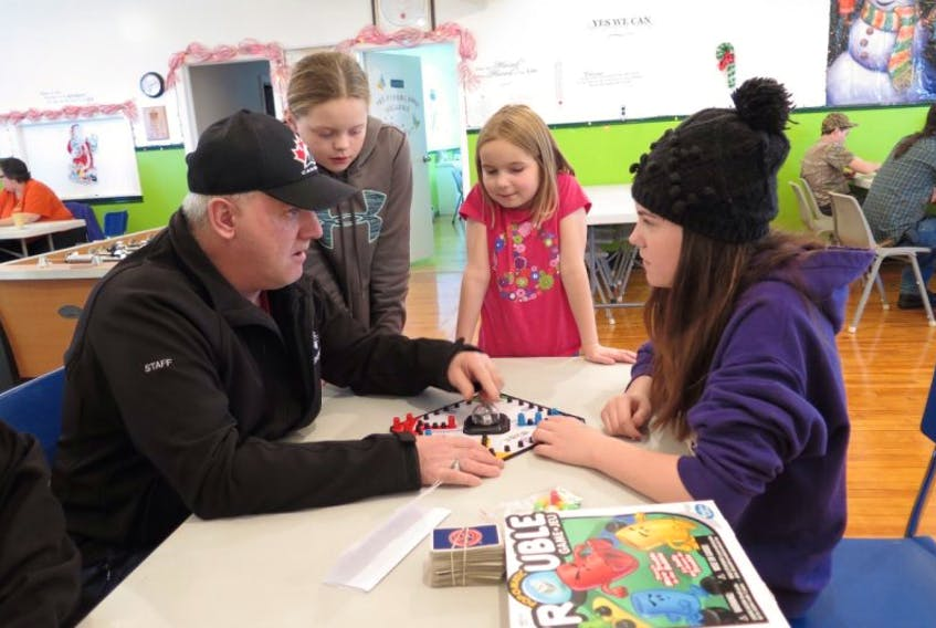 """Family Support For Our Youth Day at the JHBGC in Buchans. Among those who were there playing board games were Rob Lane, Kelli-Lynn Chippett, Savannah Savoury, and Hannah Gosse – this was a serious match of """"Trouble""""."""