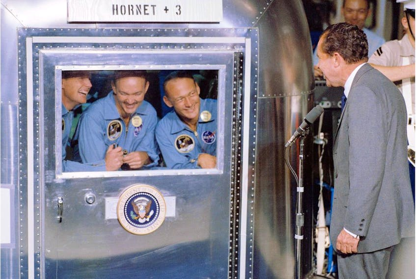 (FILES) This July 24, 1969, file photo from NASA, shows then-U.S. President Richard Nixon welcoming the Apollo 11 astronauts aboard the USS Hornet. The three were confined to the Mobile Quarantine Facility. Left to right:  Neil Armstrong, commander; Michael Collins, command module pilot; and Edwin Aldrin Jr., lunar module pilot.