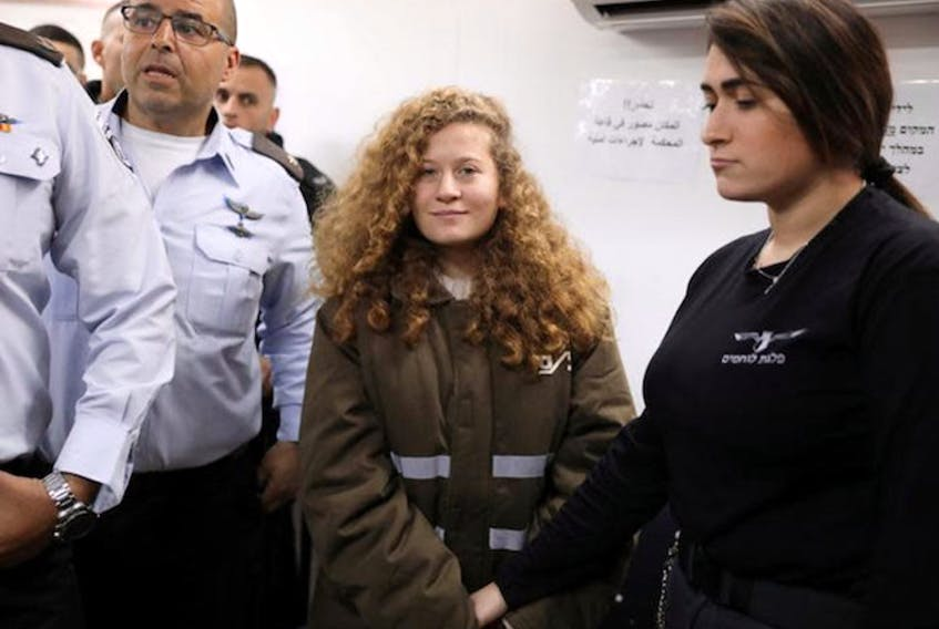 Palestinian teen Ahed Tamimi enters a military courtroom escorted by Israeli security personnel at Ofer Prison, near the West Bank city of Ramallah, January 15, 2018.   (REUTERS/Ammar Awad)