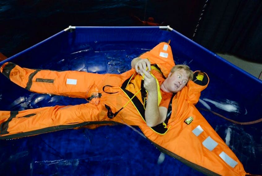 ['Alex Bernt of White Glacier demonstrates the Arctic 25 immersion suit in an ice pool at the Atlantic Canada Petroleum Show. — Photo by Keith Gosse/The Telegram<br /><br />']