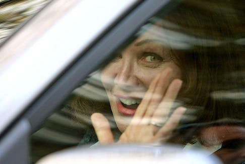 Barbara Amiel waves to the media as she drives away from her and Conrad Black's home in Toronto on May 4, 2012.