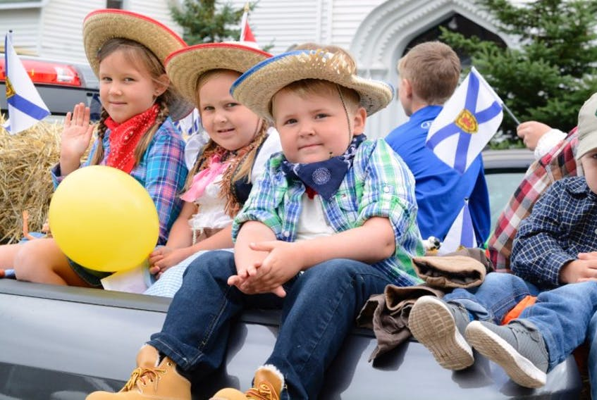 Taking a ride along the parade route are (from left) seven-year-old MacKenzie Canning, five-year-old Mirika Canning, and five-year-old Cal Wells.