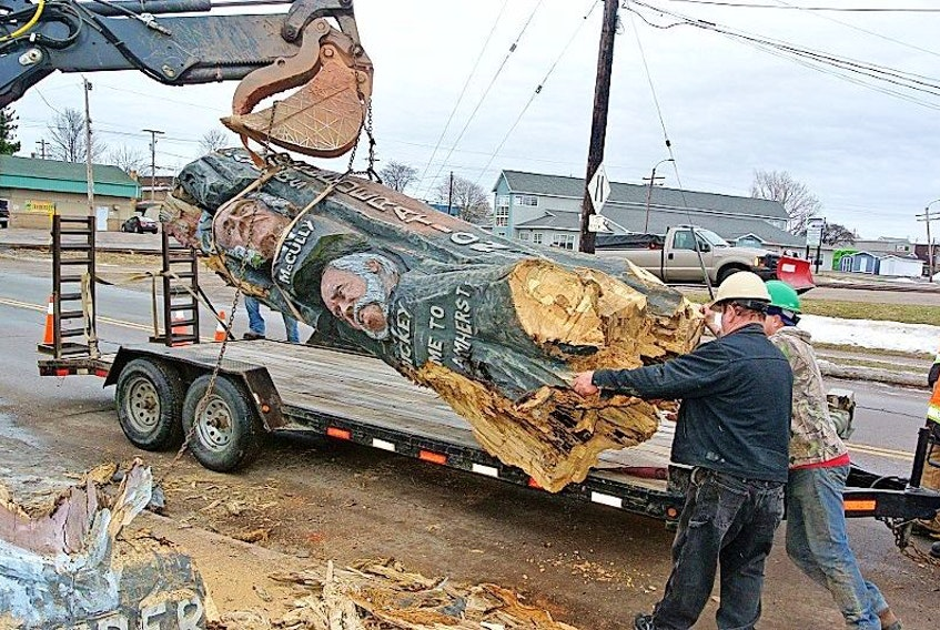 Workers from the Amherst's Public Works Department and Ken Gilbert Tree Services remove the Four Fathers of Confederation woodcarving from West Victoria Street on Wednesday. The carving had rotted to the point it was becoming a safety hazard.