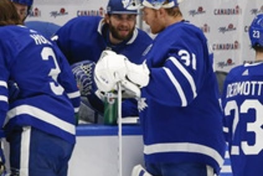 Maple Leafs goalies Jack Campbell (on the bench) and Frederik Andersen chat during a break in action on Jan. 18.