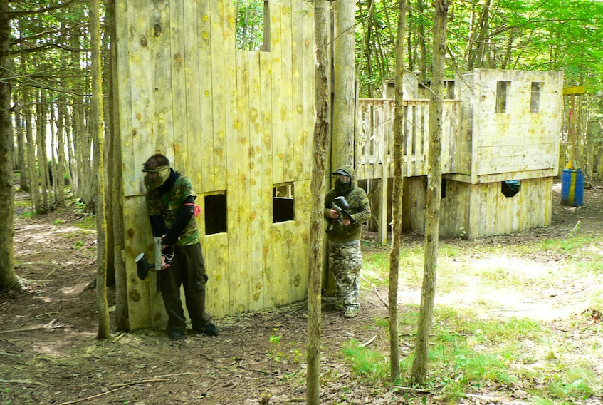 Paintball players on the defensive plot out their next move at Storm Warning's outdoor facility in Kings County. - Contributed