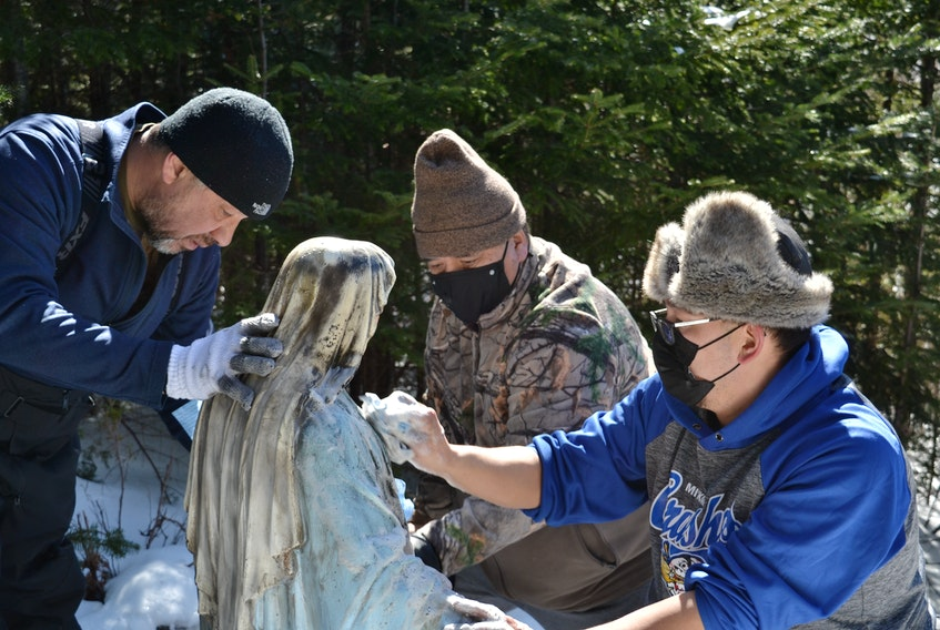 Fred Sylliboy, Walter Denny and Pierre Gould clean the blackened statue of the Blessed Mother. Denny found the statue in flames on Friday afternoon, and volunteers spent much of Saturday trying to repair the damage. ARDELLE REYNOLDS/CAPE BRETON POST