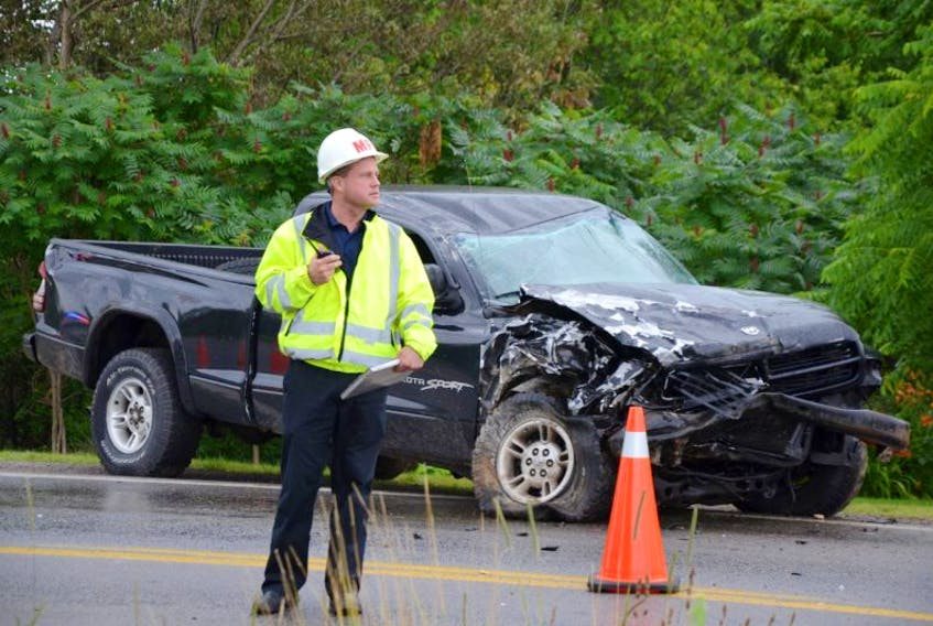 Middleton Fire Chief Mike Toole stands in front of the totaled Dodge truck that witnesses said hit another Dodge truck that turned into a campground driveway in front of it.