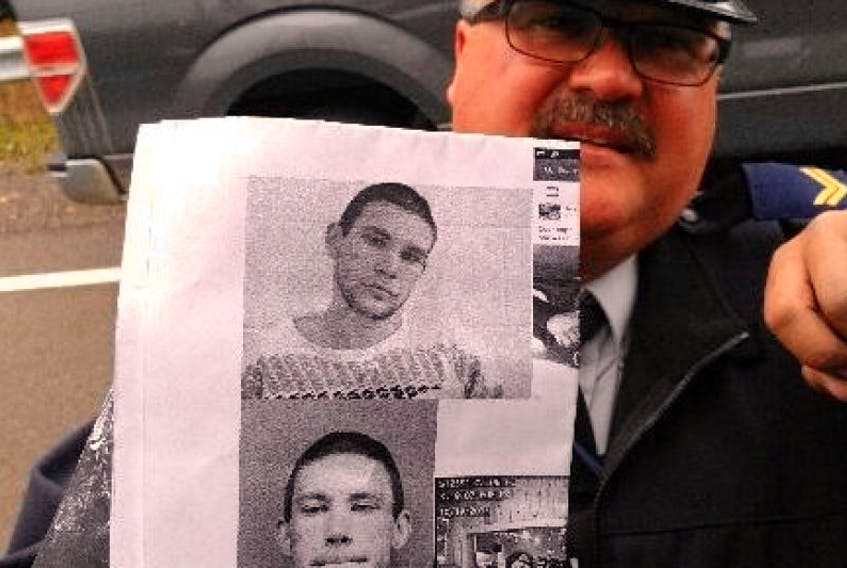 RCMP Corporal Rob Lewis shows a driver on the Shore Road outside Digby a photo of Justin Dempster on Oct. 25.