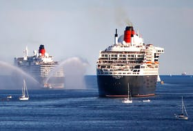 The Cunard vessels Queen Elizabeth, left, and Queen Mary 2 are feted with a water cannon last summer as they leave Halifax. - File