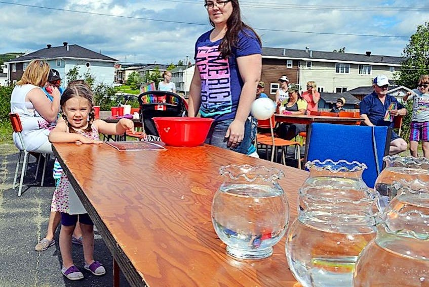 Kayla Salt, 4, daughter of Ashley Salt, has a great time throwing a ball into a fishbowl for prizes.