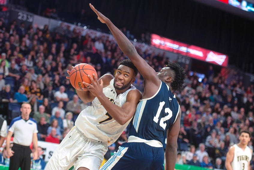 Dalhousie Tigers forward Jordan Wilson drives to the hoop against St. Francis Xavier  X-Men forward Azaro Roker during the  AUS men's basketball championships game at the Scotiabank Centre on Sunday, March 1, 2020.