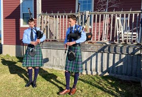 """From left, Cameron MacNeil, 14, and his brother Aidan MacNeil, 16, perform """"Amazing Grace"""" outside their home in Christmas Island, Friday morning, as a tribute to the Portapique shooting victims. The MacNeils are members of the Cape Breton University Pipe Band. CONTRIBUTED"""