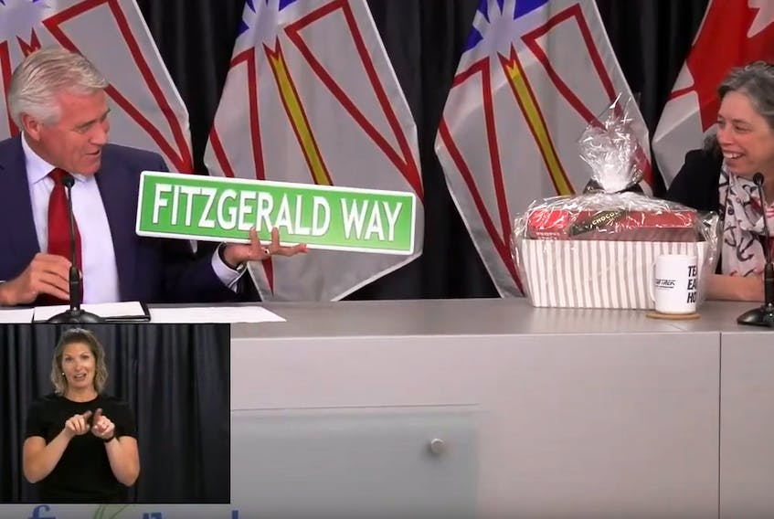 Outgoing Premier Dwight Ball presents gifts to Chief Medical Officer of Health Dr. Janice Fitzgerald Wednesday during his last appearance at the weekly COVID-19 briefings in St. John's. Inset: ASL interpreter Heather Crane. Image from video