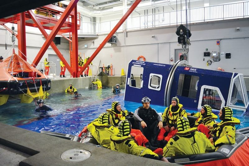 An instructor explains the features of an aviation raft to a group of offshore workers during a Basic Survival Training course. - Courtesy of Falck Safety Services