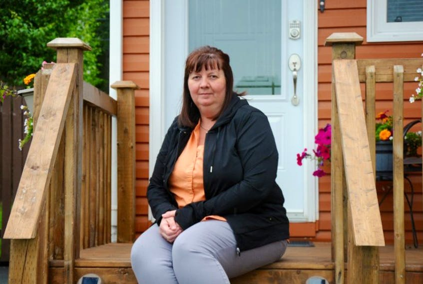 Joanne Head, secretary for the Lakeview Courts steering committee, sits on the steps of her mobile home. She's been a part of an effort to purchase the land her home sits on from Killam Properties Inc.