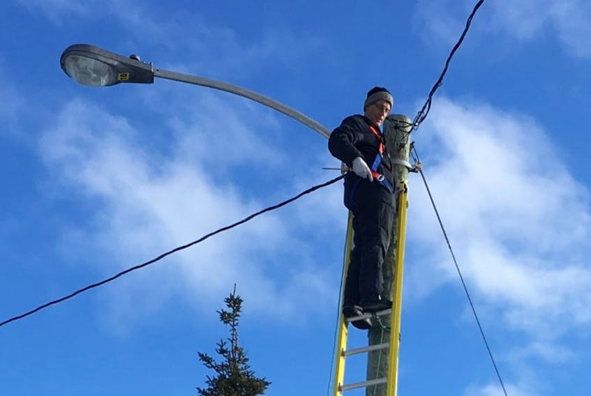 Jeremy Decker repairs an existing light at the Airport Nordic Ski Club