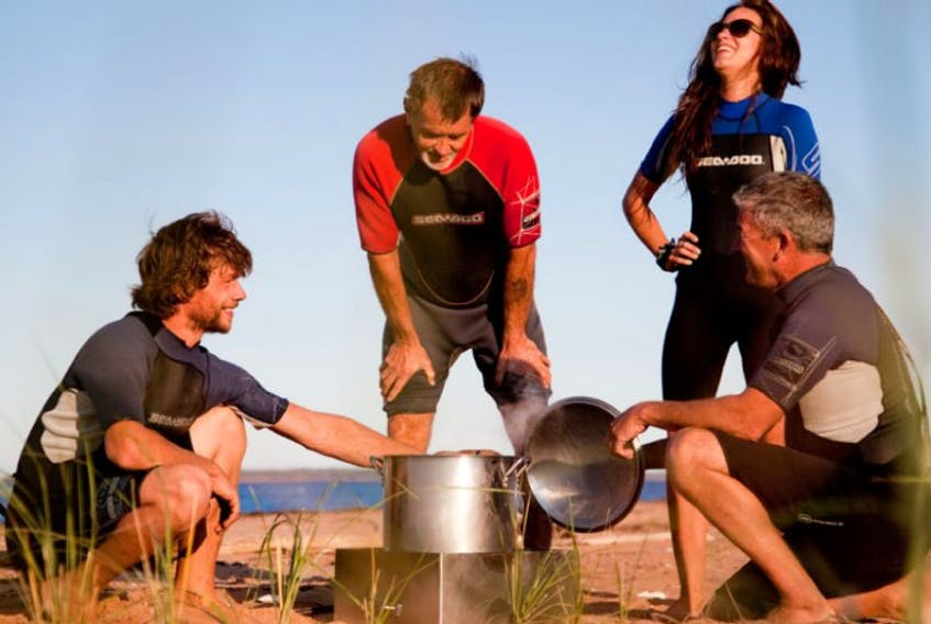 Tranquility Cove owner Perry Gotell, right, shows visitors how to steam freshly caught clams during a beach cook out.