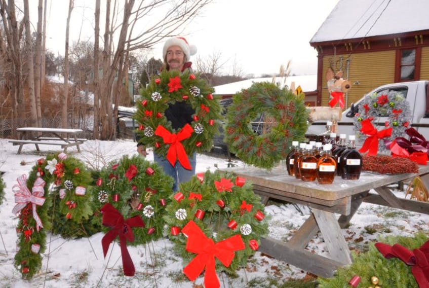 <p>Peter Burrell sold wreaths and maple syrup outside at the Holiday Spirit craft show last year in Bear River.</p>