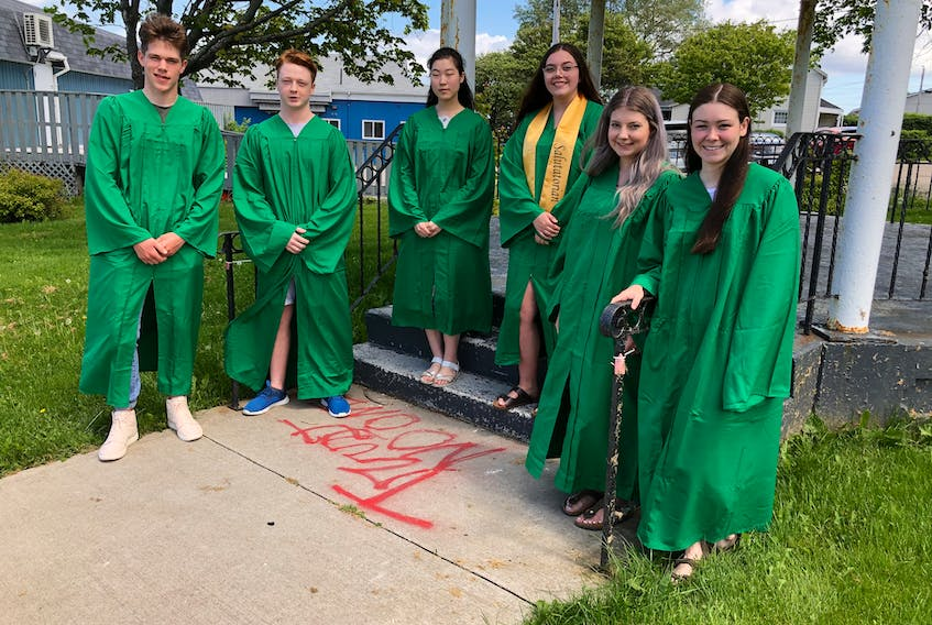 Breton Education Centre graduates gathered at William Davis Square in New Waterford for a photo on Tuesday. They will end the week with the drive-in grand march on Sunday. From left, Matthew Ross, Kyle MacKenzie, Megumi Furukawa, Vessa MacNeil, Rennee Doucette and Madison Bresowan. NICOLE SULLIVAN/CAPE BRETON POST