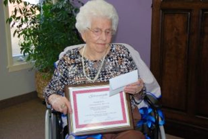 ['Jeanette Birch looks over a plaque presented to her from Summerside Mayor Bill Martin, recognizing her lifetime of commitment to family and community on the occasion of her103rd birthday. She was born in Freeland, Lot 11 on Jan. 5 1912.']