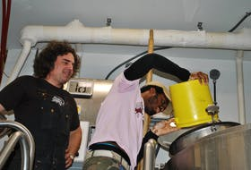 Boxing Rock co-founder and brewer Henry Pedro watches as O'Neil Miller pours the hops in the Back to Birchtown brew. O'Neil is also a fonder of the Change Is Brewing Collective. KATHY JOHNSON/TRI-COUNTY VANGUARD
