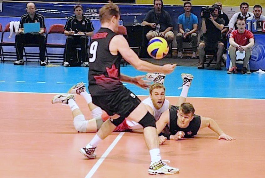 Canada's Blair Bann, second from left, and Gordon Perrin dove to keep this ball alive for Dustin Schneider during the opening set of a Federation International Volleyball (FIVB) World League match versus Bulgaria at Eastlink Arena in Summerside on Friday night.