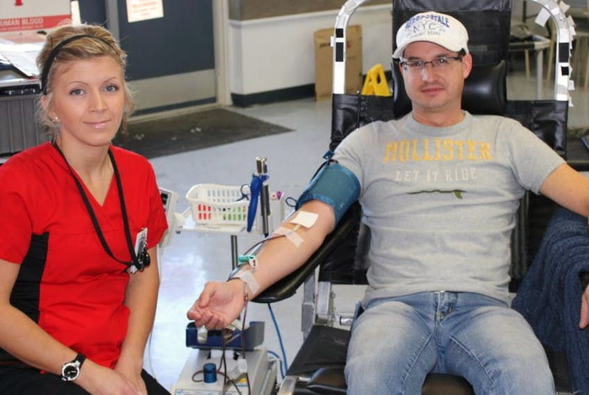 Phlebotomist (blood specialist) Sarah Charnock, left, supervises Trevor Flynn of New Minas during his blood donation March 24 at the Kentville Fire Hall March 24. Canadian Blood Services is experiencing a shortage of blood supply resulting from Atlantic Canada's winter weather