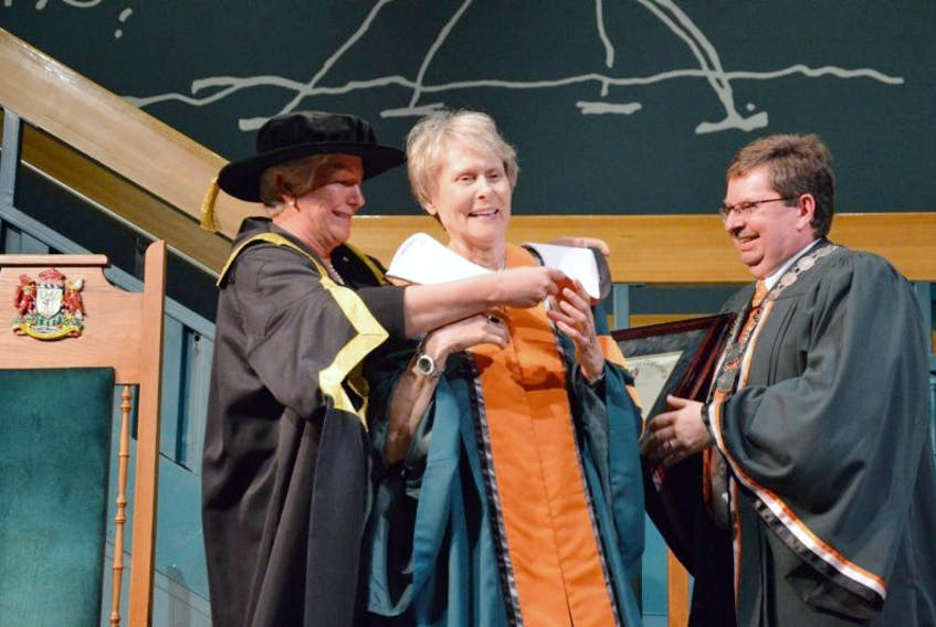 Cape Breton University chancellor Annette Verschuren, left, fixes Dr. Roberta Bondar's robes as she receives an Honourary Doctorate of Letters from the university on Saturday at a special convocation held at Baddeck's Alexander Graham Bell Museum while Dr. Dale Keefe, CBU's president and vice-chancellor, right, gets ready to shake Bondar's hand.