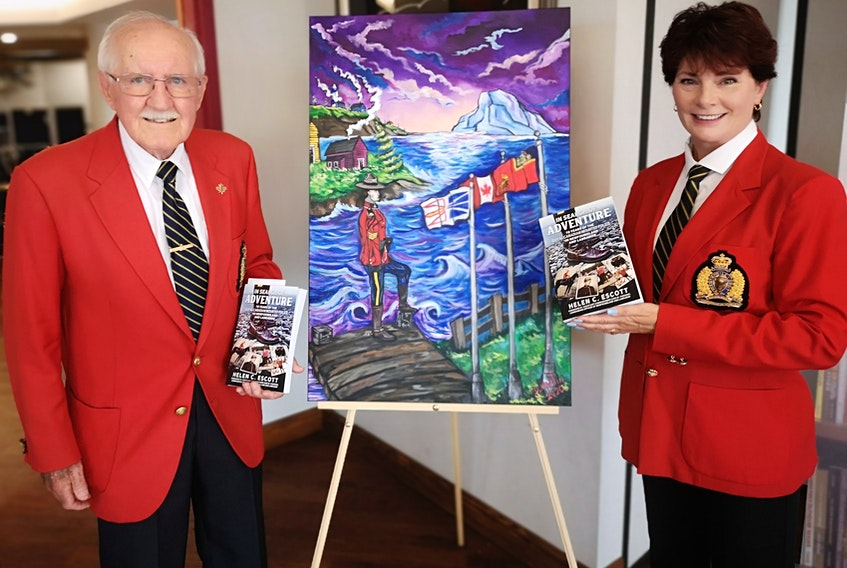 """Retired RCMP superintendent George Powell stands with Helen C. Escott at the book launch for """"In Search of Adventure — 70 Years of the RCMP in Newfoundland and Labrador."""" The painting between them is by Darrin Martin. – Andrew Waterman/The Telegram"""