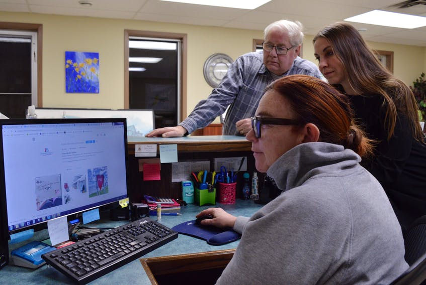 Borden-Carleton Chief Administrative Officer Wendy McIsaac, seated, Coun. Laurel Palmer-Thompson and Mayor Charles MacKenzie check out the town's social media accounts, monitoring the impact of the new town brand. Alison Jenkins/Journal Pioneer