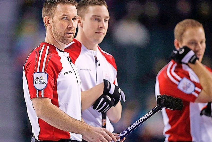 Newfoundland and Labrador skip Brad Gushue (left) stands with his temmates second Brett Gallant and lead Geoff Walker right) during bronze medal game curling action against Saskatchewan at the Brier in Calgary on Sunday<br /><br />