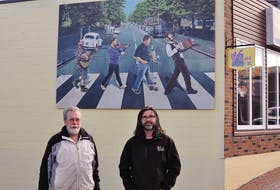 """Lorne Bishop (left) took Sheldon Power's vision and turned the image from the Beatles' """"Abbey Road"""" album cover into one featuring local musicians. The mural is a focal point on Power's Village Music shop on Broadway in Corner Brook."""