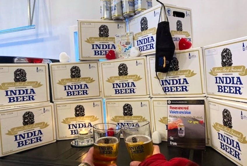 Peter Howlett clinks glasses with his wife, Wanda, surrounded by cases of Molson beer. The company sent him a surprise delivery after seeing the social media posts.