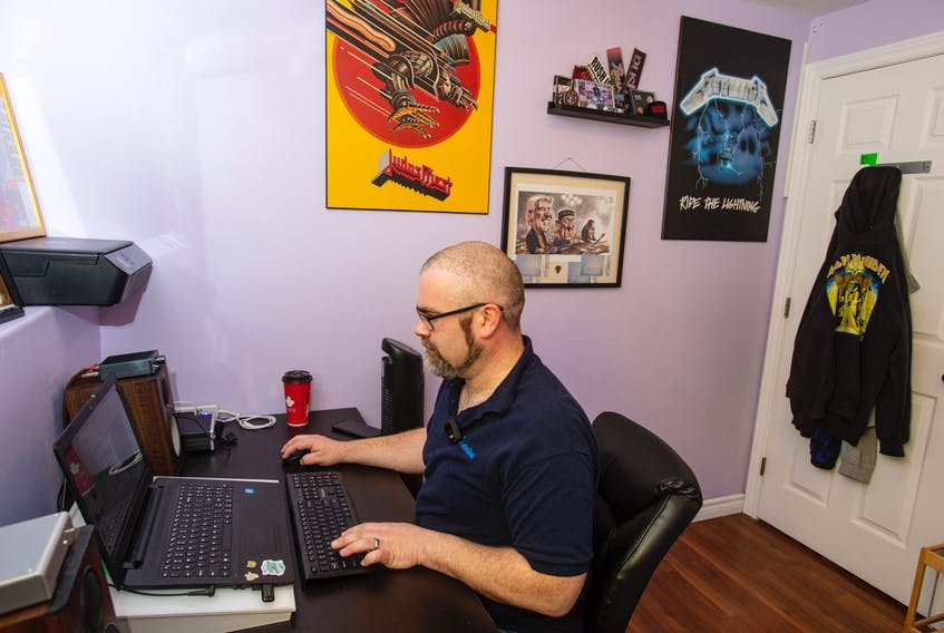 With his heavy metal poster on the wall next to him, Kyle Davis, communications coordinator with Admiral Insurance, works from his home office in Eastern Passage on Friday, Jan. 8. Ryan Taplin - The Chronicle Herald