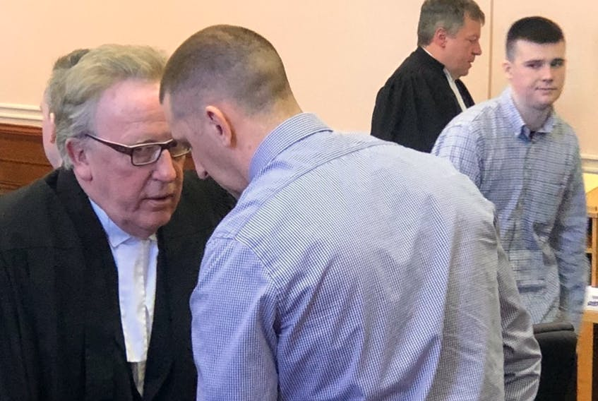 Accused murder conspirator John Squires speaks with his lawyer, Derek Hogan, following the adjournment of his trial Monday in Newfoundland and Labrador Supreme Court in St. John's. In the background is his co-accused, Brandon Glasco. The two men — and a third, Shane Clarke — have pleaded not guilty to a charge of plotting a murder in 2018. Tara Bradbury/The Telegram