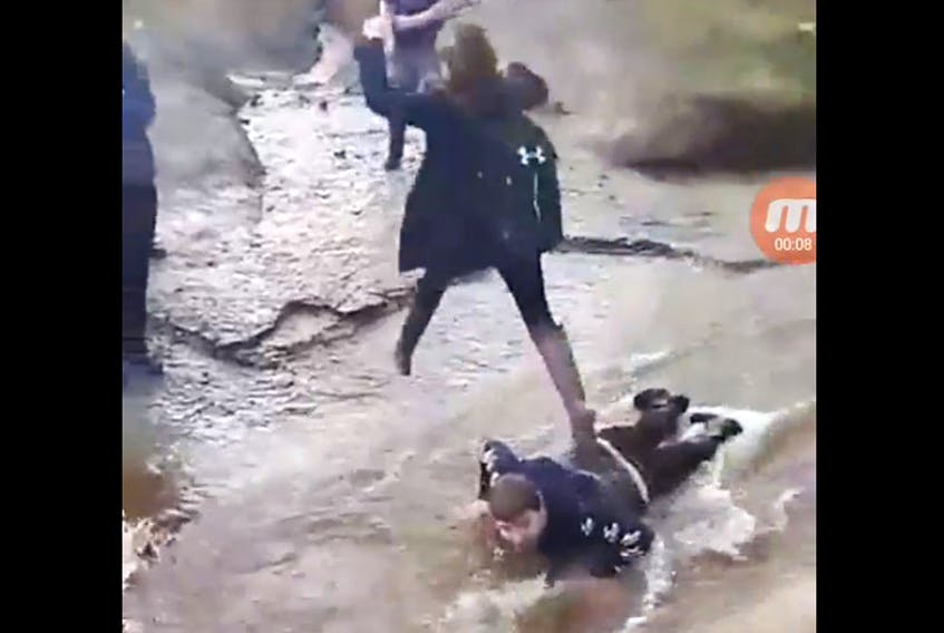 This Facebook video screen grab shows a teen lying in a stream and young girl walking on him. - Facebook