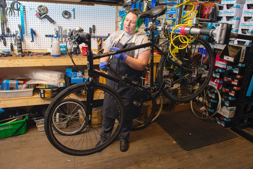 Jenna Molenaar, co-owner of Halifax Cycles & Guitars, works on a bike inside her Kempt Road shop on Thursday, May 7, 2020. Bike shops are bustling with people buying new bikes and getting their old bikes fixed up. Ryan Taplin - The Chronicle Herald