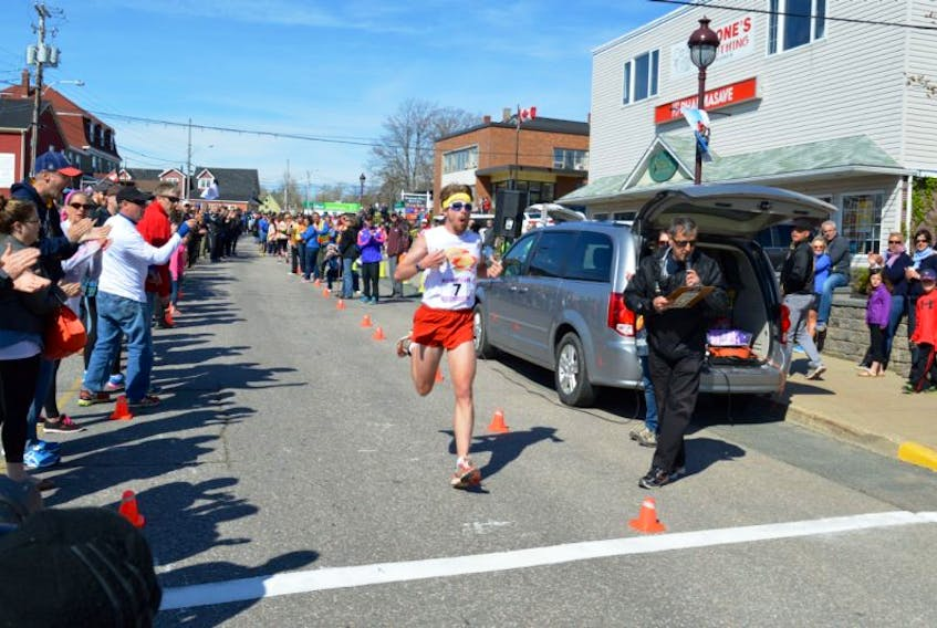 In this file photo from the 2015 Cabot Trail relay, Dan Vassallo of the Maine-iacs crosses the finish line first on Leg 17 in a new course time to help his team clinch the win for the fifth year in a row.