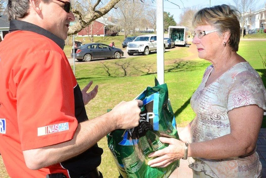 <p><span>Cameron Beach, owner of the Canadian Tire store in Charlottetown, presents Dianne Gillis with a bag of grass seed as part of the company's Tested for Life in Canada program.</span></p>