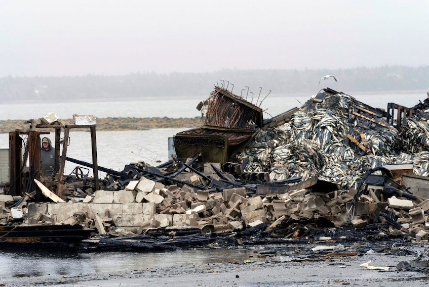 A person looks at the remains of a lobster pound after it burnt in Middle West Pubnico, N.S., on Oct. 17.
