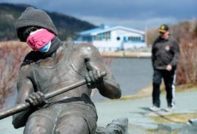 Someone has placed a mask on the Regatta rower statue on the shore of Quidi Vidi Lake. The Quidi Vidi boathouse is in the background.