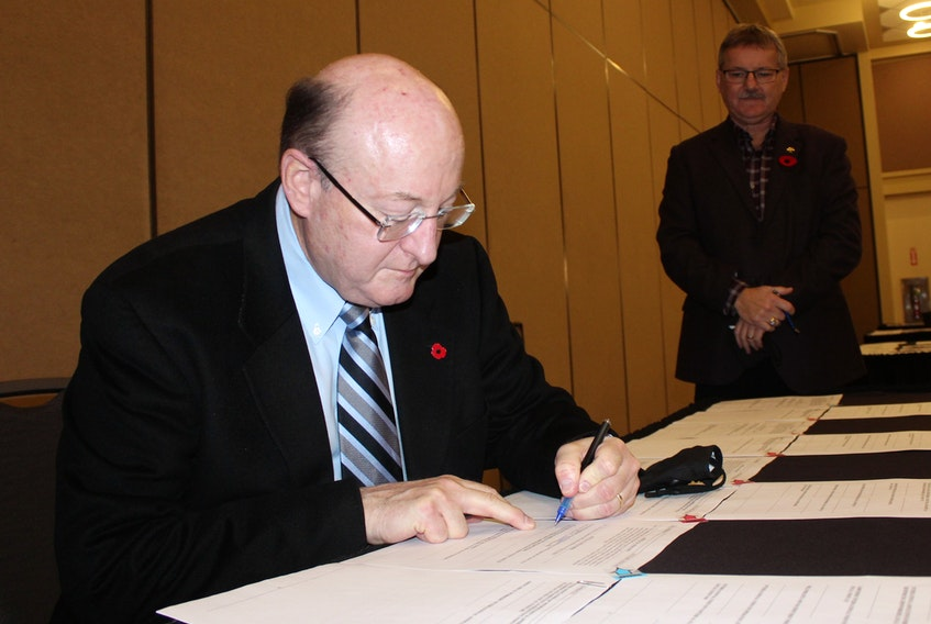 Robert Shepherd, president of the Nova Scotia Construction Labour Relations Association, signed a new five-year contract with Cape Breton Building and Construction Trades Council on Tuesday at the Membertou Trade and Convention Centre. Looking on is Jack Wall, president of the trades council, who also signed the contract on Tuesday along with members of various trades across the island. GREG MCNEIL • CAPE BRETON POST