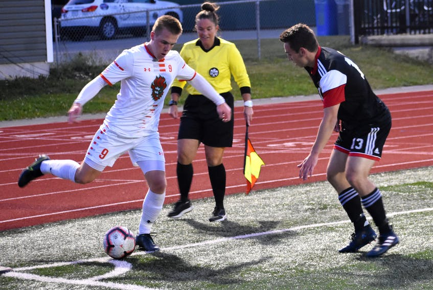 In this file photo, Charlie Waters of the Cape Breton Capers, left, attempts to work his way around Nick Ellingwood of the New Brunswick Reds during Atlantic University Sport men's soccer action at the Cape Breton Health Recreation Complex. In June, the AUS cancelled the fall sports season due to the COVID-19 pandemic. JEREMY FRASER/CAPE BRETON POST