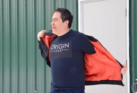 Origin Coast founder and chief executive officer Michael Fong braves Wednesday's sub-zero temperature to show off the shirted logo of his new company Origin Coast. The Sydport-based operation has been granted Health Canada licenses to cultivate cannabis for the recreational and medical markets. DAVID JALA/CAPE BRETON POST