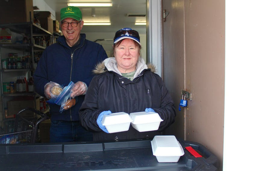 Jerry Pocius, left, and Florence MacNeil hold up takeout meals from Loaves and Fishes in Sydney, which are being served to clients while the dining area is closed. NICOLE SULLIVAN/CAPE BRETON POST