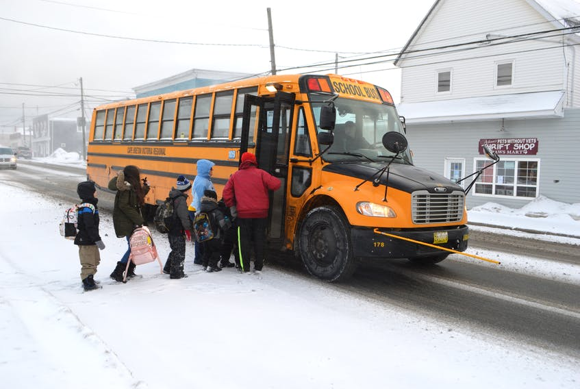 Volunteers Al Crawley, right, and his partner Kelly Brown assist students getting on the school bus at a Cape Breton-Victoria Regional Centre for Education stop on Victoria Road near Henry Street, Whitney Pier. The CBVRCE says this is one of the bus stops where they get the most complaints from bus drivers regarding motorists not heeding the red flashing light on the bus. Crawley said he sees several motorists ignoring the red lights on the school bus every week. Sharon Montgomery-Dupe/Cape Breton Post