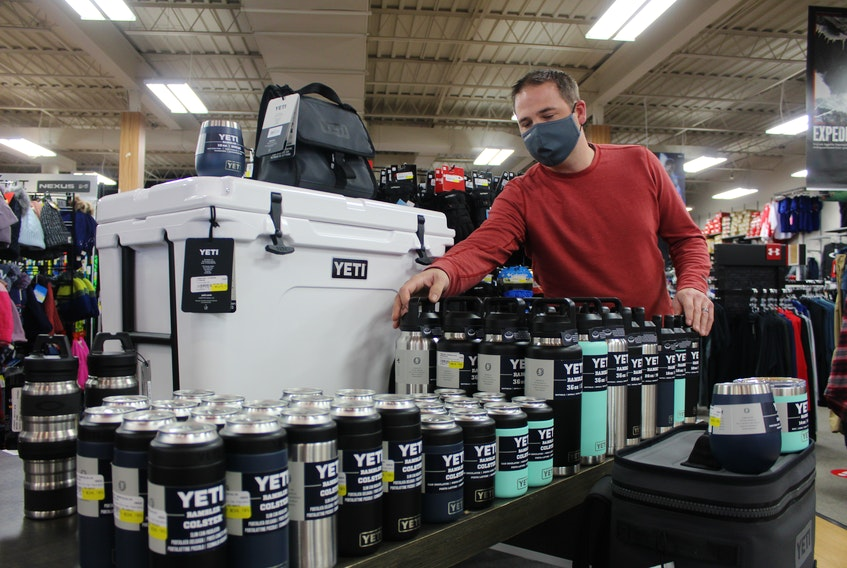 Andrew Rudderham, owner of Rudderham's Source For Sports, adjusts stock at the Sydney River sporting goods store this week. Adding staff for the holidays is a common store practice each year, but he's not yet sure if that'll be the case this year. GREG MCNEIL/CAPE BRETON POST
